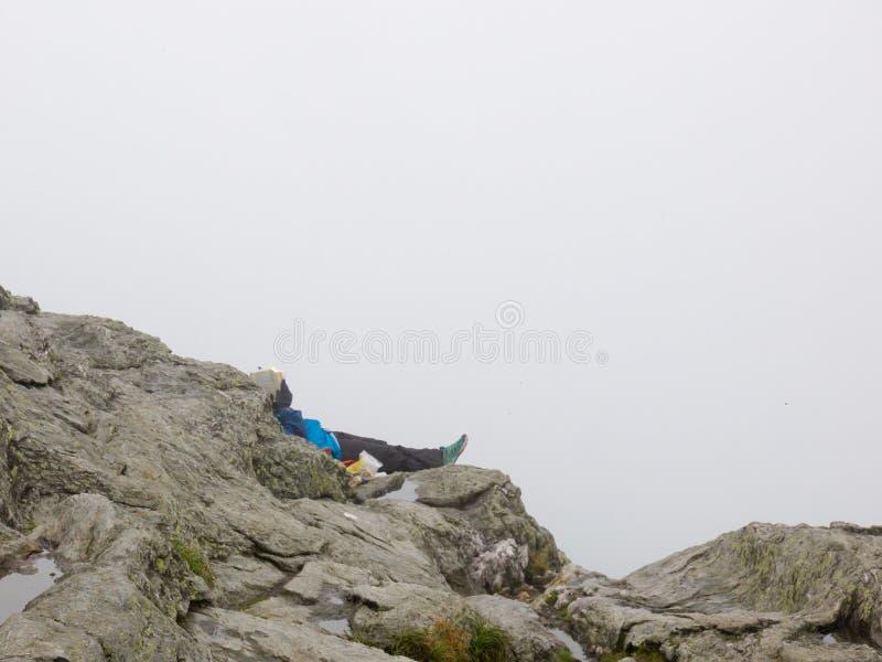 Una mujer sola, acostándose, lee un libro en el top de una montaña en un día de verano de niebla fotografía de archivo