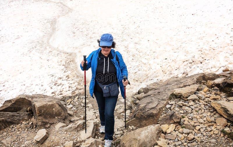 Una mujer sola en el equipo turístico hikking en un glaciar en las montañas fotos de archivo