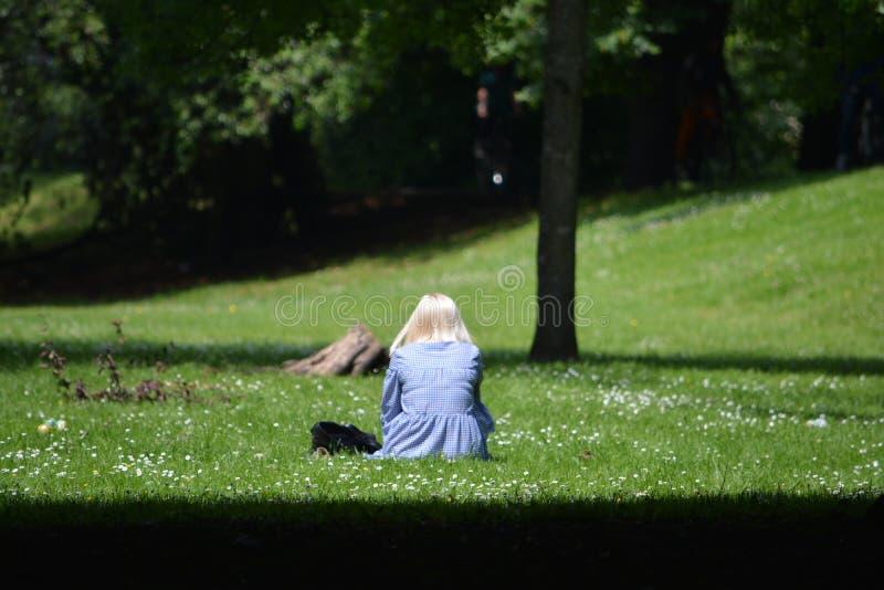 Una mujer sola en un día soleado brillante y hermoso en Sophia Gardens Cardiff foto de archivo