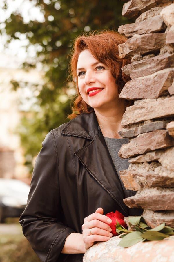 Una mujer sonriente cuarenta-cinco-año-vieja con los labios rojos y el pelo rojo mira a escondidas hacia fuera de detrás la pared imagen de archivo libre de regalías