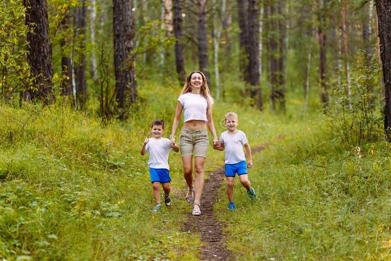 Una mujer sonriente delgada caucásica y dos niños alegres de los preescolares en las camisetas blancas funcionadas con a lo largo foto de archivo libre de regalías