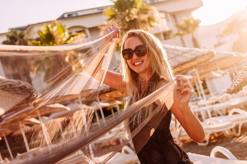 Una mujer sonriente joven mira la cámara en la luz del sol contorneada en la playa Gente y verano foto de archivo