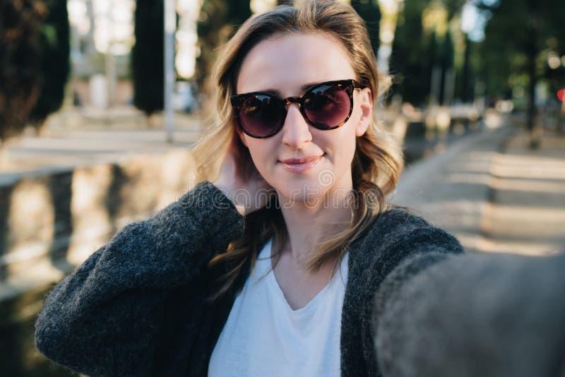 Una mujer sonriente joven se está colocando en un parque y está haciendo un selfie La muchacha en gafas de sol toma imágenes de s imagen de archivo