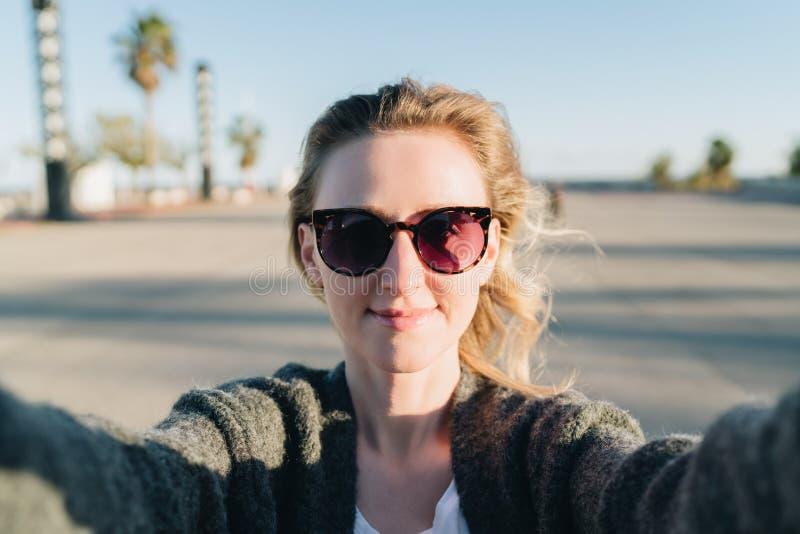 Una mujer sonriente joven se está colocando en un parque y está haciendo un selfie La muchacha en gafas de sol toma imágenes de s fotografía de archivo libre de regalías