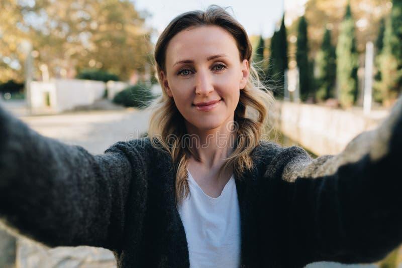 Una mujer sonriente joven se está colocando en un parque y está haciendo un selfie La muchacha toma imágenes de sí misma Retrato  foto de archivo libre de regalías
