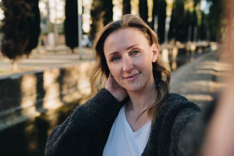 Una mujer sonriente joven se está colocando en un parque y está haciendo un selfie La muchacha toma imágenes de sí misma Retrato  fotografía de archivo
