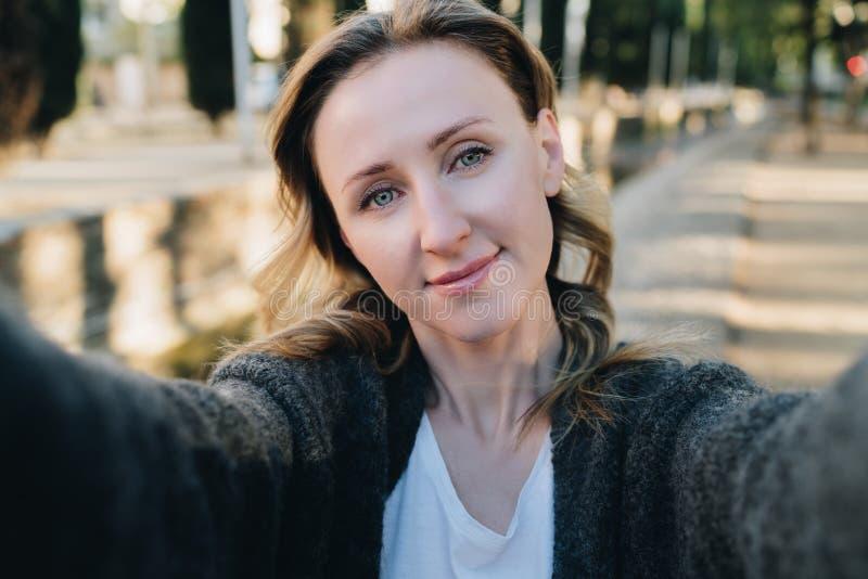Una mujer sonriente joven se está colocando en un parque y está haciendo un selfie La muchacha toma imágenes de sí misma Retrato  foto de archivo
