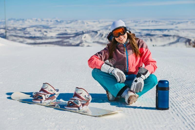 Una mujer sonriente joven se sienta en una cuesta de montaña con una snowboard y un termo fotos de archivo
