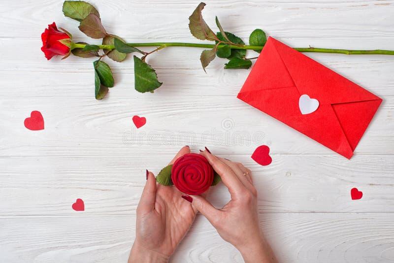 Una mujer sostiene una caja con un anillo un regalo amado Fondo de día de San Valentín con una rosa roja, un regalo y un sobre co fotografía de archivo libre de regalías