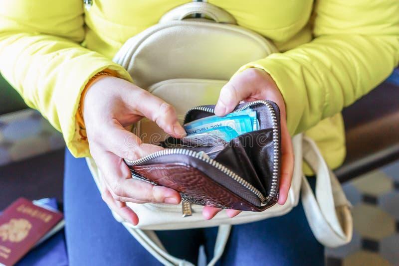 Una mujer sostiene una cartera y cuenta el dinero ruso imágenes de archivo libres de regalías