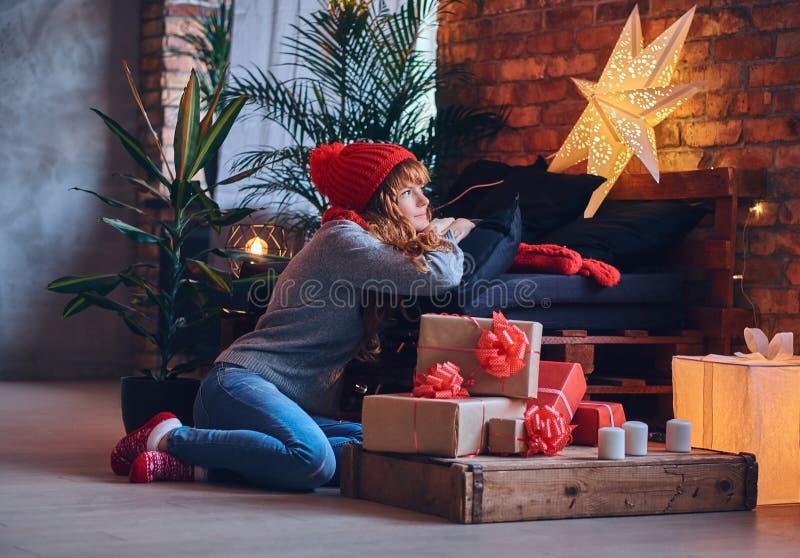 Una mujer sostiene un regalo de la Navidad en una sala de estar con interi del desván imagen de archivo
