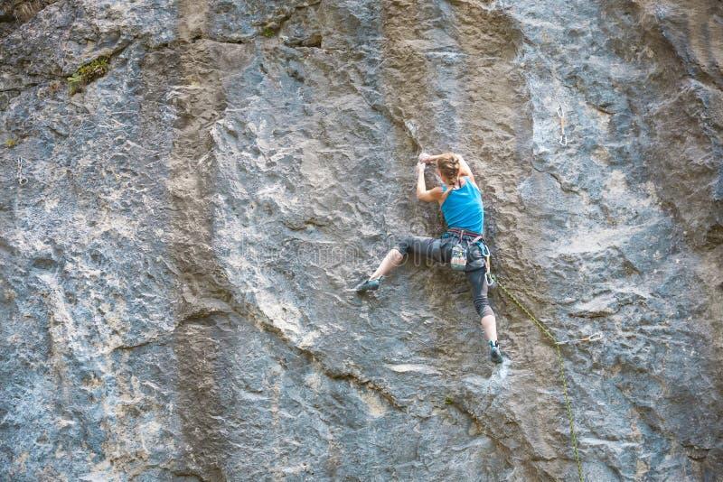 Una mujer sube la roca fotos de archivo
