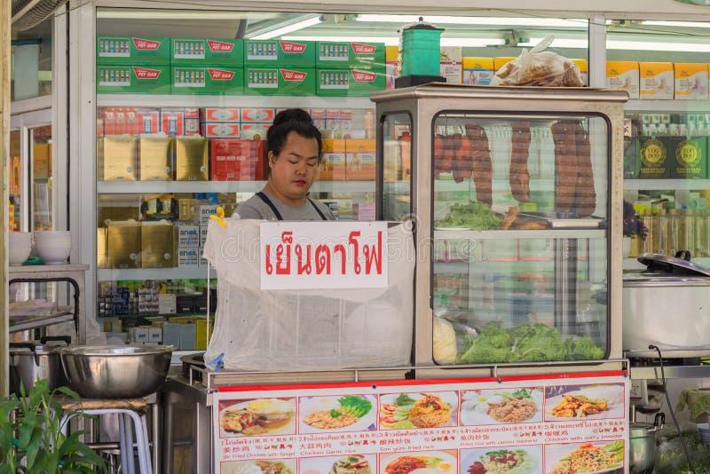 Una mujer tailandesa cocinaba la comida en un pequeño restaurante móvil imagen de archivo