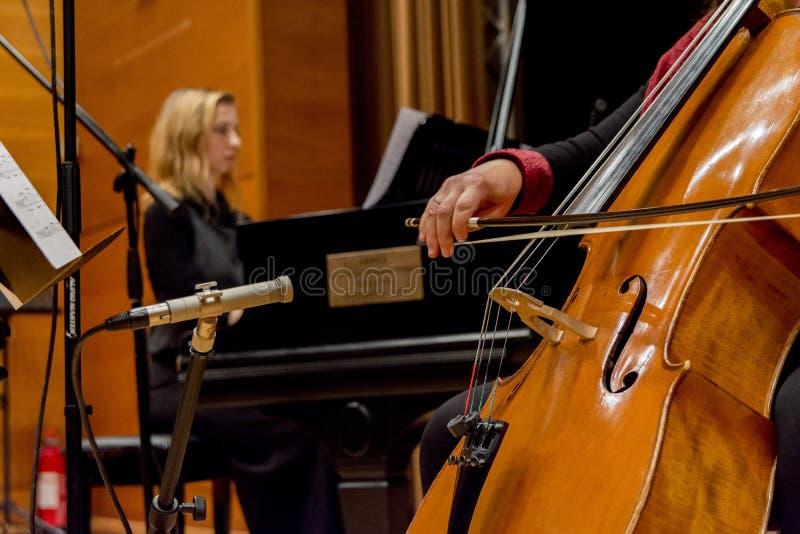 Una mujer toca el violoncelo en un concierto fotos de archivo