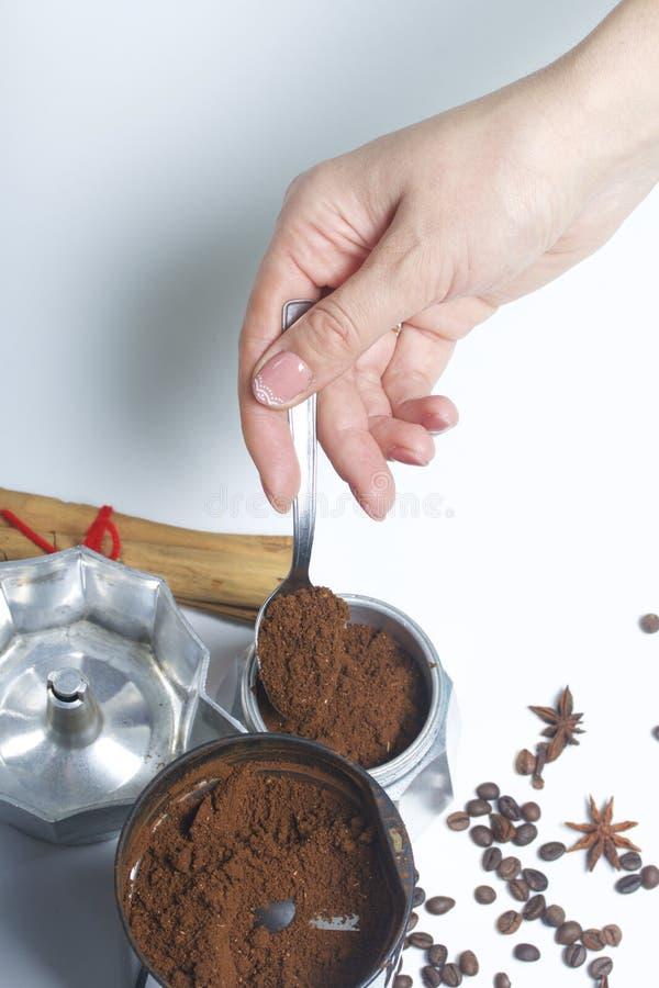 Una mujer toma una cucharada de café molido de una amoladora de café y la pone en una máquina del café del géiser imagen de archivo