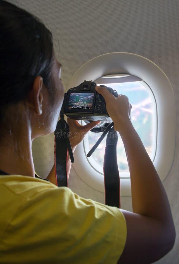 Una mujer toma la foto de una ventana del avión fotografía de archivo libre de regalías