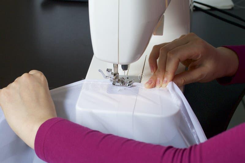 Una mujer trabaja en una máquina de coser Ella cose las cortinas en la ventana imágenes de archivo libres de regalías