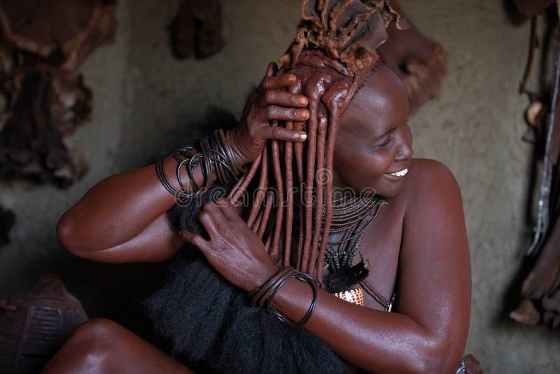 Una mujer tradicional de la tribu del himba que hace su procedimiento de la belleza fotografía de archivo