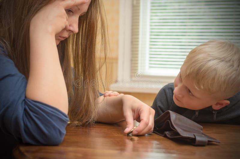 Una mujer triste en la tabla piensa las monedas pasadas Cartera vacía - el hijo del muchacho calma a la madre fotos de archivo