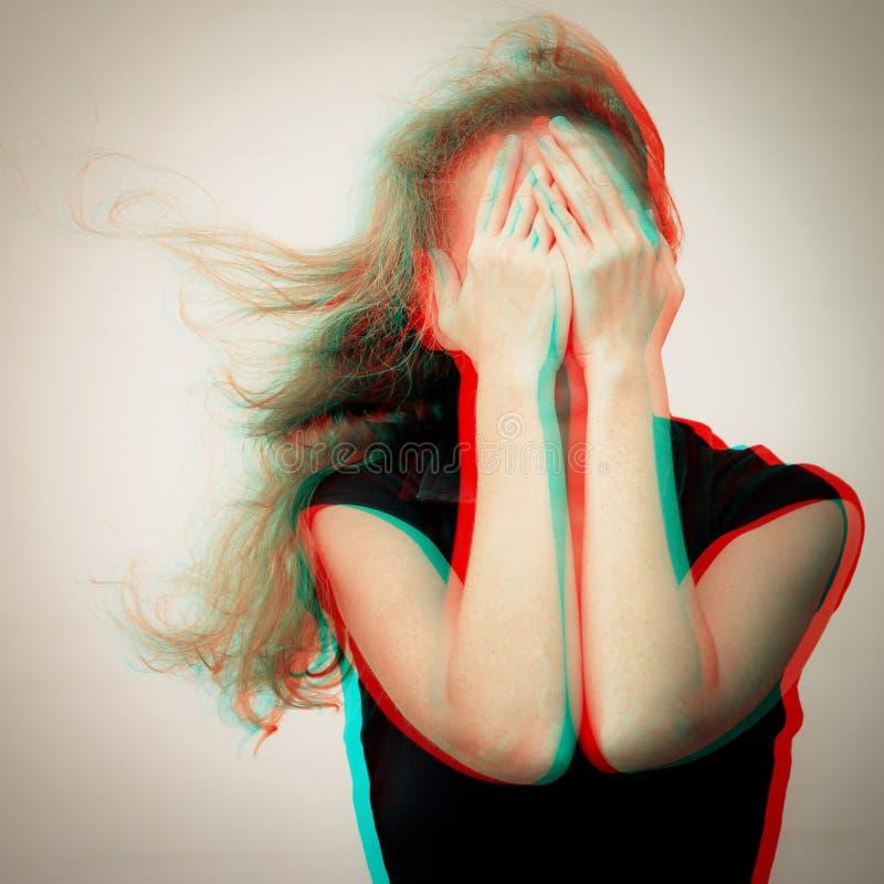 Una mujer triste que se coloca cerca de una pared y que lleva a cabo su cabeza en su h imagen de archivo libre de regalías