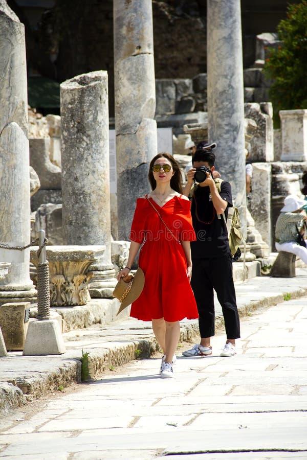 Una mujer turística que se vistió en rojo está caminando con el donante de las actitudes para la fotografía y el turista que el h foto de archivo