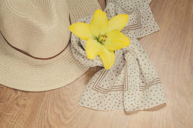 Una mujer va el vacaciones o en un viaje - un sombrero y una bufanda ligera con los lunares mienten en un fondo de madera Humor r imagenes de archivo