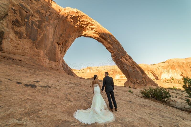Una mujer vietnamita en su vestido de boda presenta con su novio en el desierto estéril de Moab, Utah fotos de archivo
