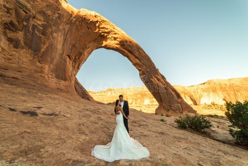 Una mujer vietnamita en su vestido de boda presenta con su novio en el desierto estéril de Moab, Utah imagen de archivo