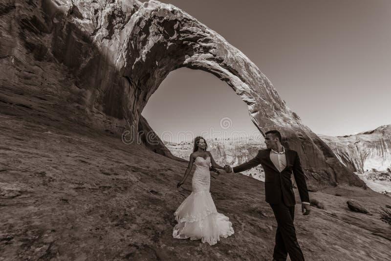 Una mujer vietnamita en su vestido de boda presenta con su novio en el desierto estéril de Moab, Utah imágenes de archivo libres de regalías