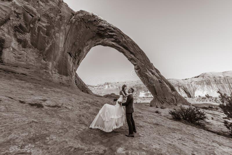 Una mujer vietnamita en su vestido de boda presenta con su novio en el desierto estéril de Moab, Utah foto de archivo libre de regalías