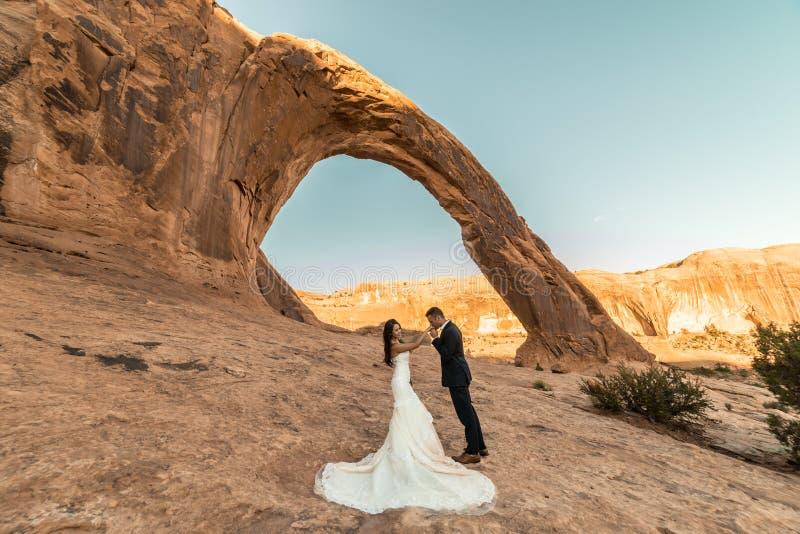 Una mujer vietnamita en su vestido de boda presenta con su novio en el desierto estéril de Moab, Utah fotografía de archivo libre de regalías