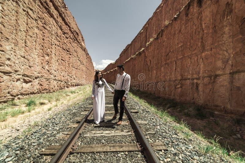 Una mujer vietnamita en un vestido de boda del traditionall presenta con su novio en el desierto estéril de Moab, Utah fotos de archivo libres de regalías