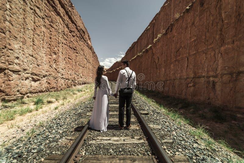 Una mujer vietnamita en un vestido de boda del traditionall presenta con su novio en el desierto estéril de Moab, Utah foto de archivo