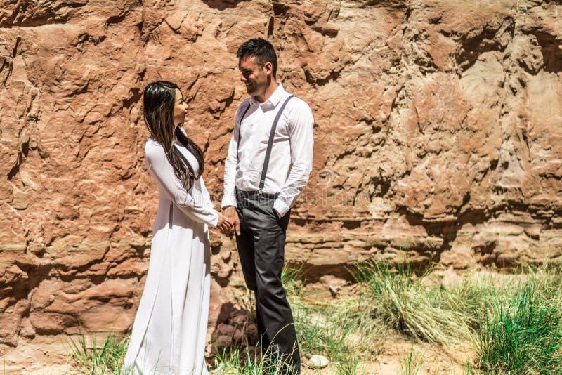 Una mujer vietnamita en un vestido de boda del traditionall presenta con su novio en el desierto estéril de Moab, Utah fotografía de archivo