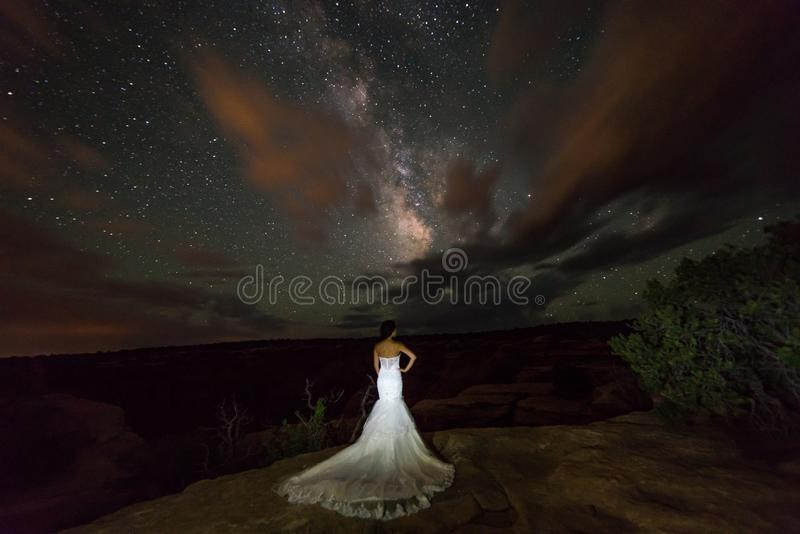 Una mujer vietnamita en un vestido de boda presenta en el desierto estéril de Moab, Utah en la noche imagen de archivo libre de regalías