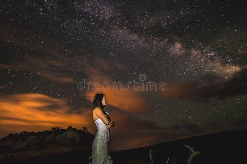 Una mujer vietnamita en un vestido de boda presenta en el desierto estéril de Moab, Utah en la noche fotografía de archivo