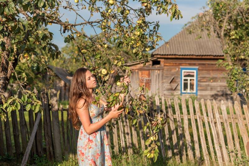 Una mujer virginal joven se coloca cerca de la cerca del jardín delante de una casa vieja del pueblo y la cierra los ojos en los  fotos de archivo