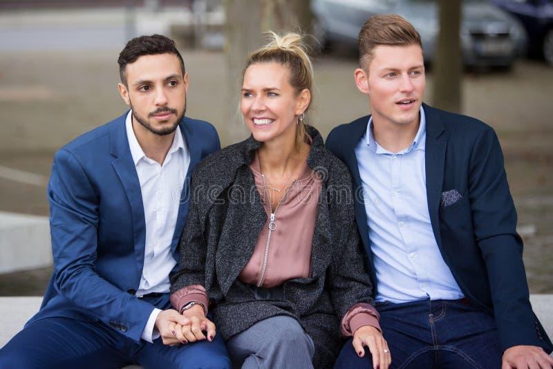 Una mujer y dos hombres que se sientan en banco junto foto de archivo libre de regalías