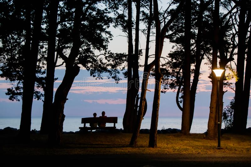 Una mujer y un hombre que se sientan en un banco y que hacen frente a la puesta del sol en la playa foto de archivo