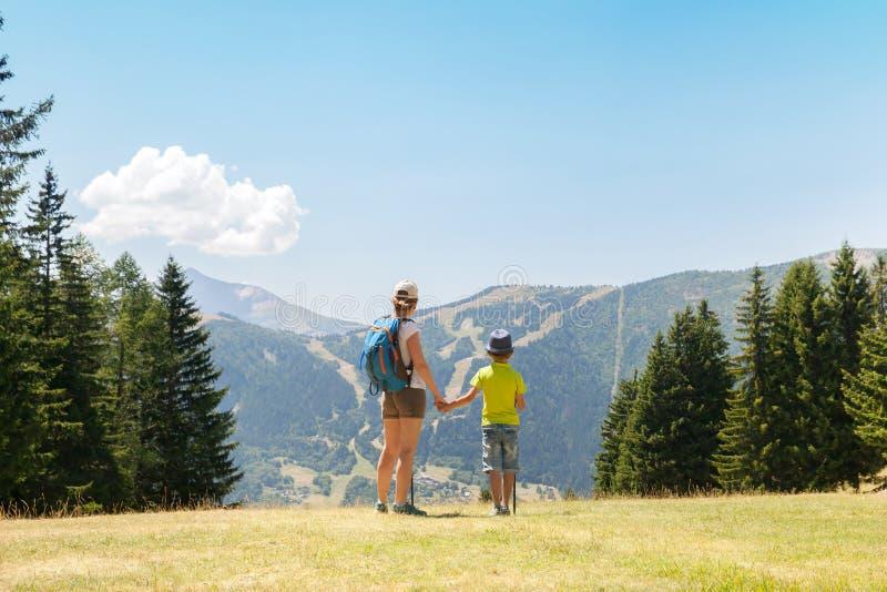 Una mujer y un muchacho están caminando en montañas fotografía de archivo