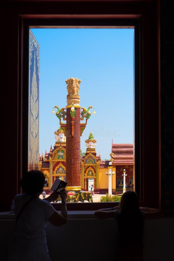 Una mujer y un niño mayores hacen las fotos en el templo Luz en la ventana imagenes de archivo