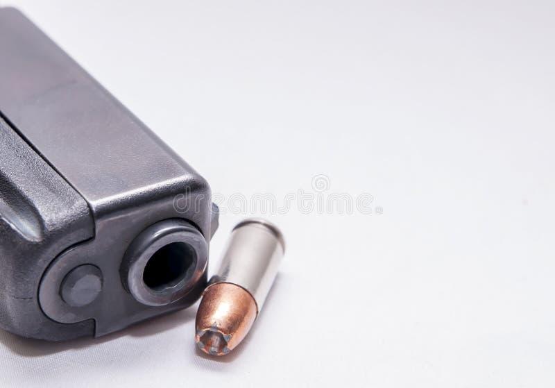 Una museruola nera della pistola di 9mm con una singola pallottola vuota 9mm del punto accanto  immagini stock libere da diritti