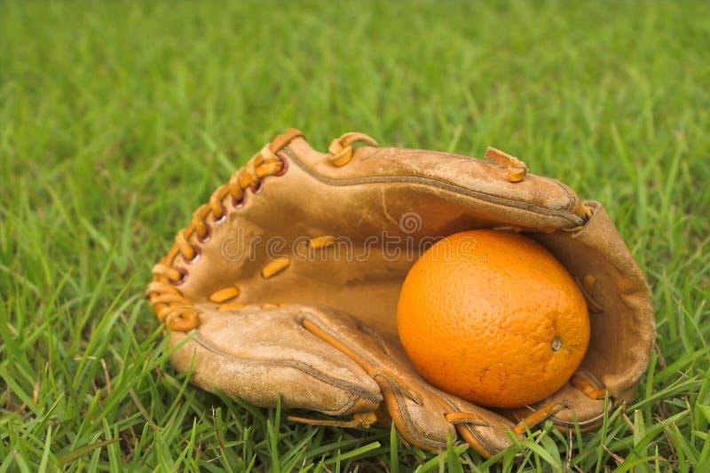 Una naranja en un guante de béisbol fotos de archivo