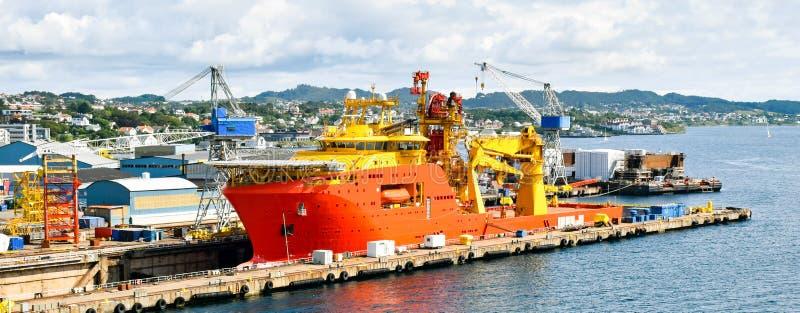 Una naranja grande y un buque costero coloreado amarillo OCV de la construcci?n est? en una dique seco de un astillero y se est?  imagenes de archivo