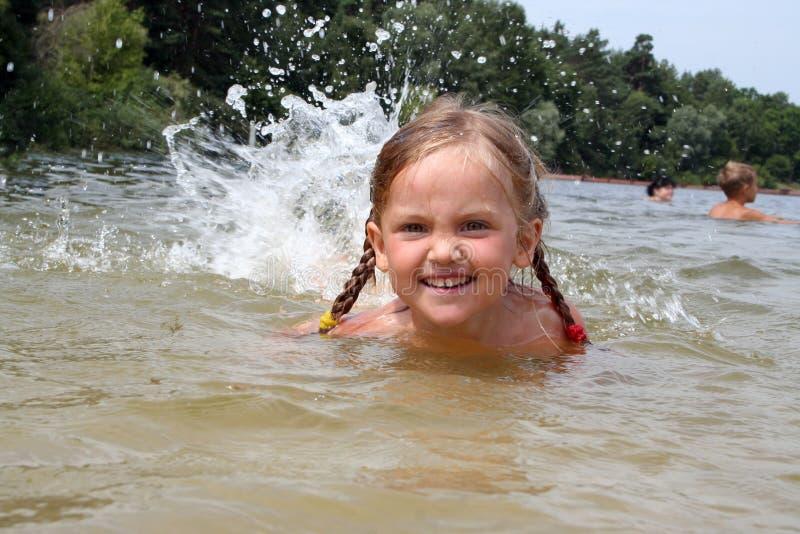 Una natación sonriente hermosa de la niña en el río con splas fotos de archivo