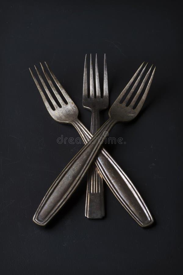 Una natura morta concettuale di tre forcelle d'argento d'annata immagine stock