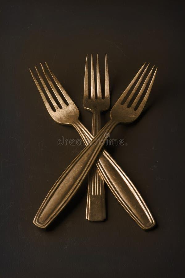 Una natura morta semplice di tre forcelle dell'annata dell'oro immagine stock