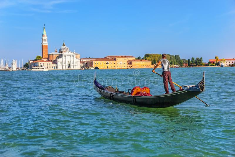Una navegación del gondolero a la isla de San Giorgio Maggiore en la laguna veneciana imagenes de archivo