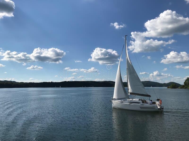 Una navegación del velero en un río/un lago Actividades al aire libre Contra la perspectiva de bosque, de las montañas y del ciel foto de archivo