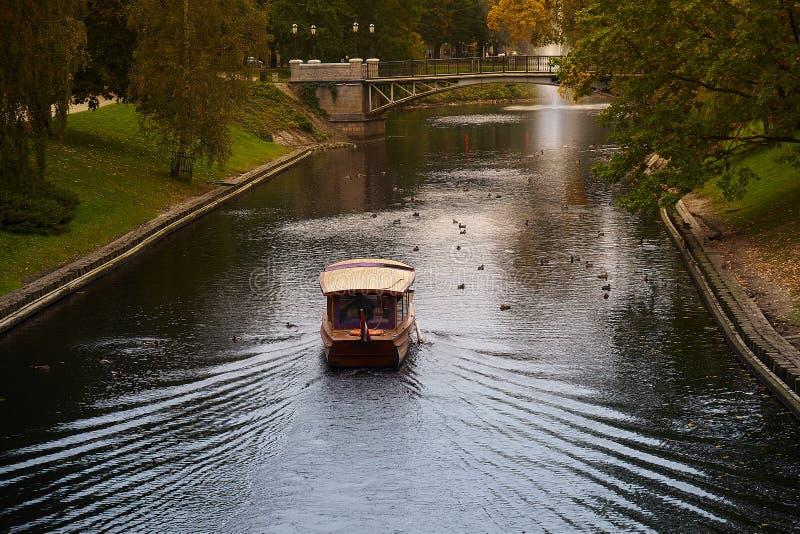 Una navigazione della barca nel parco vicino al teatro nazionale lettone di balletto e di opera a Riga, Lettonia immagini stock